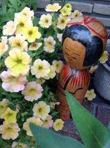 ねこの郵便局の大家さんの花に囲まれて幸福。秋田こけし